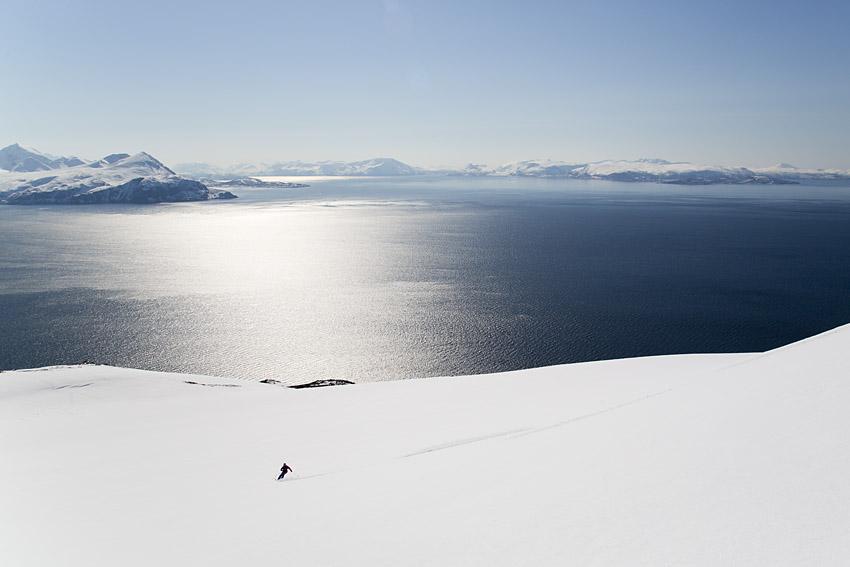 Bergsguiden Jimmy Halvardsson på väg ner från toppen av Trolltinden, med Lyngen i bakgrunden.
