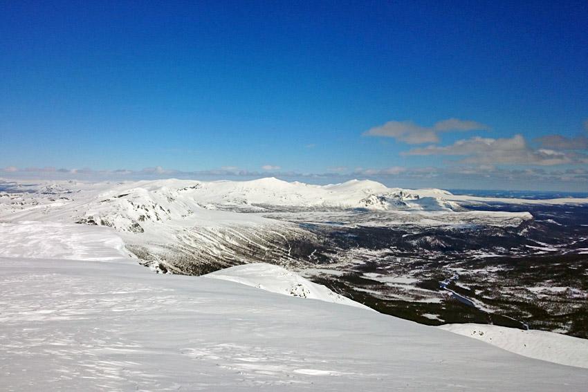 Utsikt från toppen av Borkafjället, Kittelfjäll med skidanläggning syns i bakgrunden. Lägg märke till hängdrivorna till höger i bilden, håll avstånd.